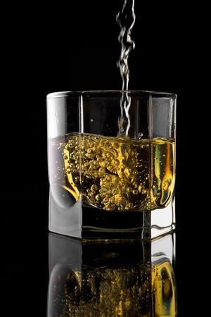 Glas whisky op een zwarte achtergrond.