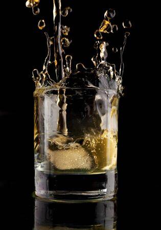 intoxicant: Bicchiere di whisky su sfondo nero. Whiskey splash in un bicchiere. Whisky con ghiaccio.