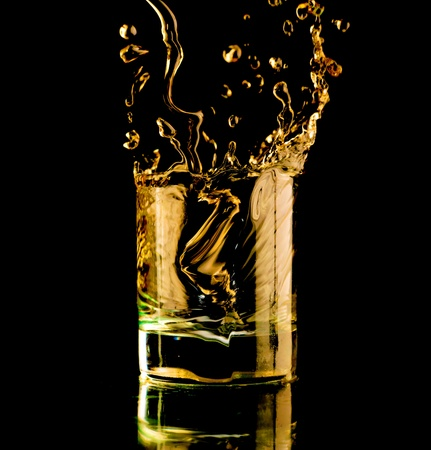 Glass of whisky on a black background. Spray and splash.