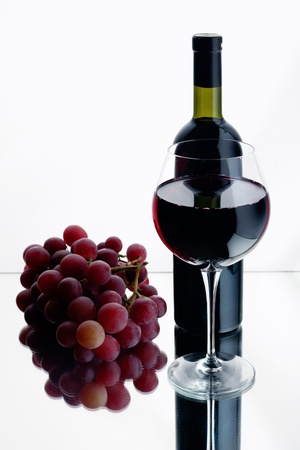 Still-life with bottle and glass of red wine over white background. photo