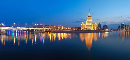 Night Moscow. Moscow River. A kind from Krasnopresnenskaya quay on hotel Ukraine and on the New Arbat bridge. Panorama. 版權商用圖片