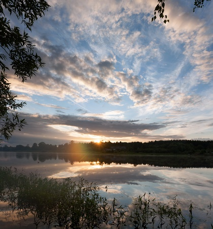 Sunrise over the river. The first rays of sun. Stock Photo - 15521711