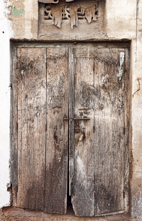 Old dilapidated wooden door. Rajasthan, India photo