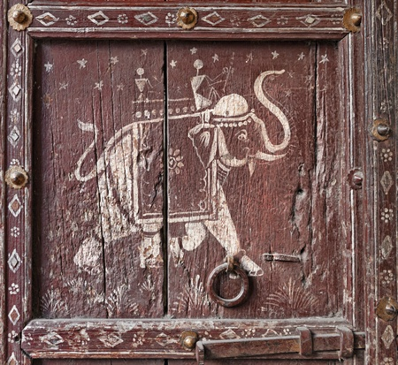 Old wooden door with a picture of an elephant. Fragment. Rajasthan, India photo