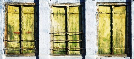 Three old windows with wooden shutters, background photo