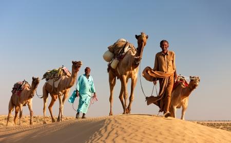 Sam, INDIA - 28 november: Een onbekend kameel man is zijn kamelen in de Thar woestijn in de buurt van Jaisalmer op 28 november 2012 in Sam, Rajasthan, India. Redactioneel