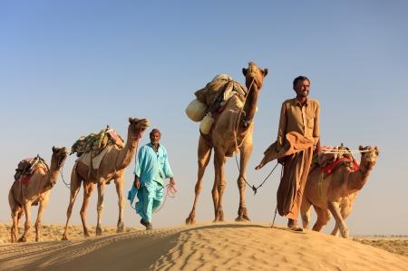 Sam, INDIA - NOVEMBER 28: An unidentified camel man is leading his  camels across the Thar desert near Jaisalmer on November 28, 2012 in Sam, Rajasthan, India. Stock Photo - 18645592