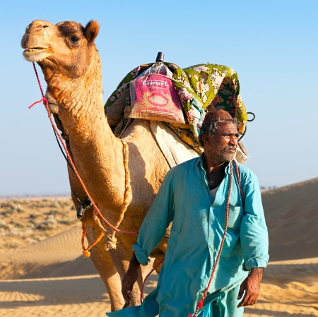 Sam, INDIA - NOVEMBER 28: An unidentified camel man is leading his camel across the Thar desert near Jaisalmer on November 28, 2012 in Sam, Rajasthan, India.
