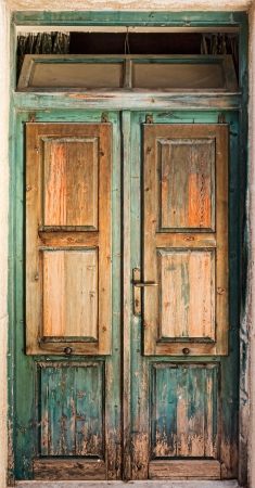 Oude houten deur met een raam aan de top