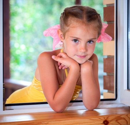 A portrait of a six years' girl  in the window in the afternoon. photo
