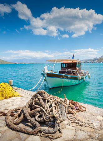 redes de pesca: Barco de pesca en la costa de Creta con cuerda marina y red de pesca en el primer plano. Foto de archivo