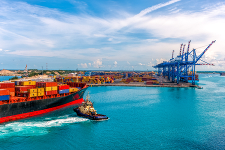 delivers: CONTAINER PORT OF FREEPORT GRAND BAHAMAS ISLAND - OCT., 8, 2014: Container ship delivers cargo to the port.
