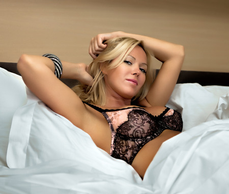 Young sexy blond woman in the bed photo