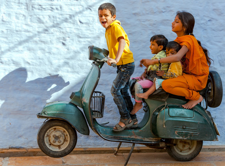 JAISALMER, INDIA - 28 november: Een niet-geïdentificeerde Indiase kinderen spelen met een oude scooter in Jaisalmer Fort op 28 november 2012 in Jaisalmer, India. Jaisalmer Fort is de leefbare fort in India.