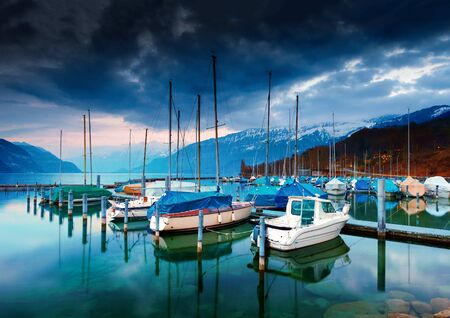 oberland: Boats and yachts on lake Thun at night. Bernese Oberland, Switzerland.