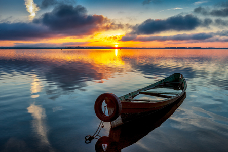 Sunrise on Lake Seliger with an old boat in the foreground, Tver region, Russia.