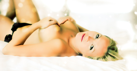 Young sexy woman lying on white sheet photo