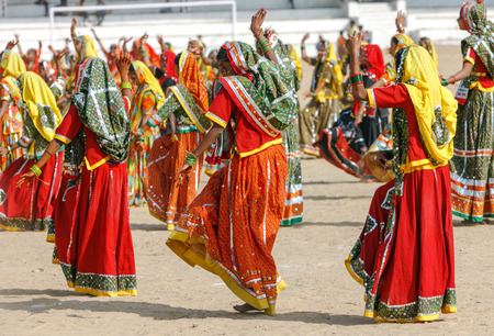 veiled:  Indian girls in colorful ethnic attire dancing at Pushkar fair, Pushkar, Rajasthan, India, Asia