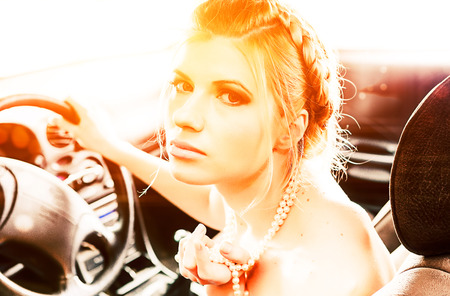 drivers seat: Young Woman in a pearl necklace sat In the drivers seat of her car Stock Photo
