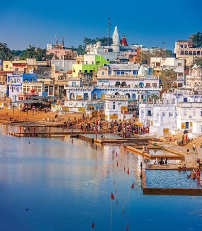 a bathing place: PUSHKAR, INDIA - NOVEMBER 20, 2012: Hindu pilgrims bathing in sacred Lake Pushkar (Sarovar) on ghats. Countless people in colourful attire gather to take a dip in the Holy Lake and pray to deities.