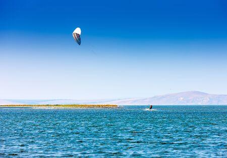 kitesurfer glides on water surface