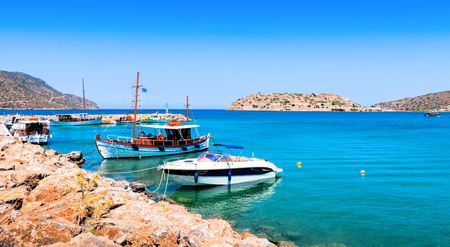 Tourist and fishing boats at the pier of the village of Plaka, near the island of Spinalonga. Crete, Greece.