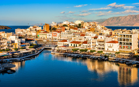 edge: Agios Nikolaos, Crete, Greece. Agios Nikolaos is a picturesque town in the eastern part of the island Crete built on the northwest side of the peaceful bay of Mirabello.?