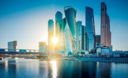 Wolkenkratzer Moskau International Business Center über Moskwa-Fluss und Bagration-Brücke. Schöne Aussicht von der Uferpromenade gegen die untergehende Sonne. Russland