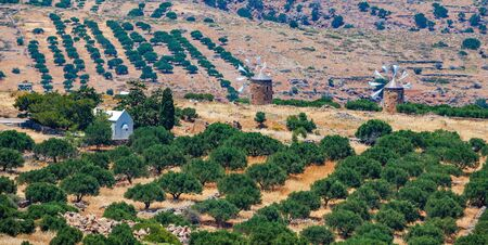 Old windmills and a small white Church in the mountains, among the olive trees on the island of Crete, Greece.