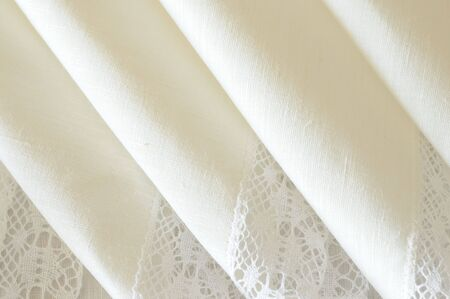 a detail of folded white linen napkins adorned with lace photo