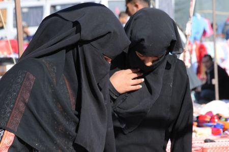 bedouin: two bedouin women in traditional dress  at souk