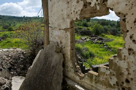 golan: bullet traces and rubbles of war against the pastoral view of Golan Heights,Israel