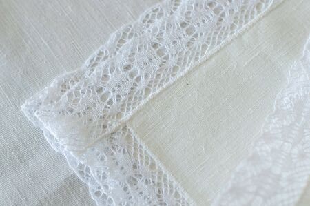 a detail of a  folded white linen napkin adorned with lace photo