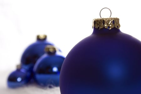 Arrangement of blue matt and shiny Christmas baubles on white fur
