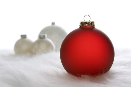 Arrangement of red and white Christmas baubles on white fur Stock Photo