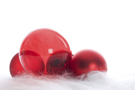 Arrangement of red Christmas baubles on white fur