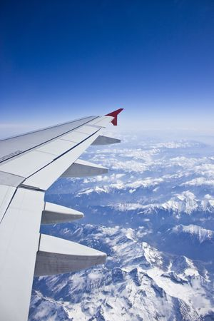 Flying over the alps, snow capped mountains, view of airplane wing