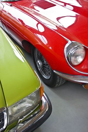 Old english car in red and old german car in green Stock Photo