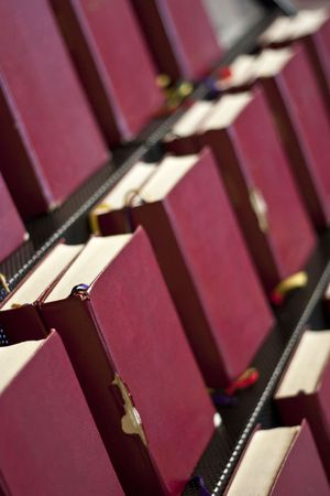 Old red bibles in a book stand in a church