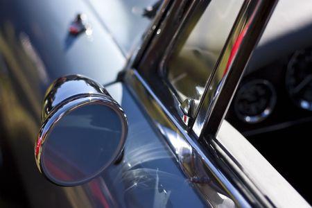 Sporty chrome rear mirror on blue vintage roadster