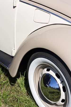 Classic car with steel rims with chrome center caps and whitewall tires Stock Photo