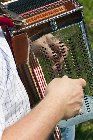 Man playing accordion with hand reflection on chrome