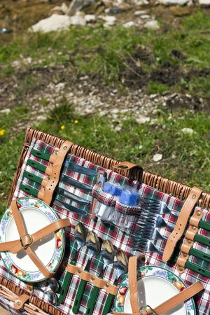 Set of dishware in the picnic basket in meadow