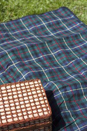 Picnic basket on plaid blanket on meadow