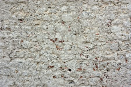 Very old brickwall with aged grey plaster