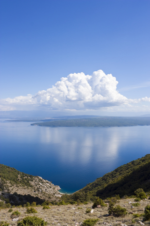 Small bay on croatia island cres, view to island krk with some clouds on blue sky