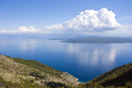 Small bay on croatia island cres, view to island krk with some clouds on sky Stock Photo