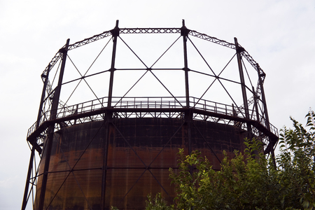 Very old and rusty gas storage tank ruin with tree Stock Photo