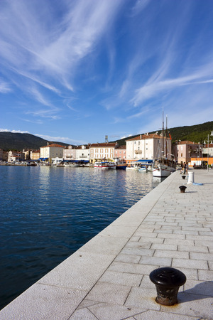 Some bollards and a sailing ship in harbor of cres on island cres in croatia