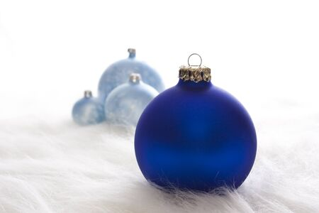 Arrangement of some blue christmas baubles on white fur Stock Photo